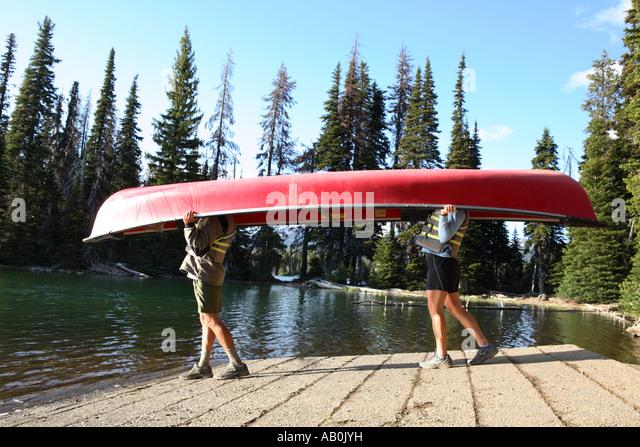 Paare, die zum See mit dem Kanu über ihre Köpfe hinweg Stockbild