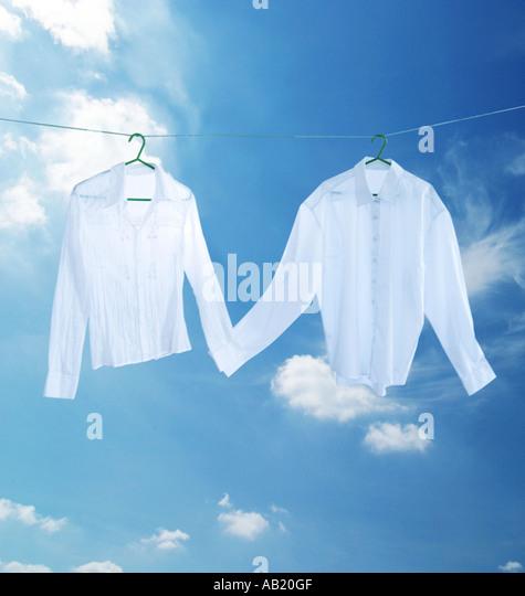 weiße Hemden auf eine Wäscheleine, die Hand in Hand Stockbild
