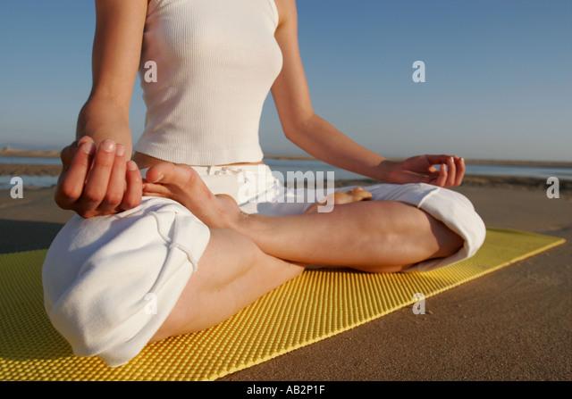 gekreuzten Beinen der Frau in der Meditation sitzen auf gelben Yogamatte Stockbild