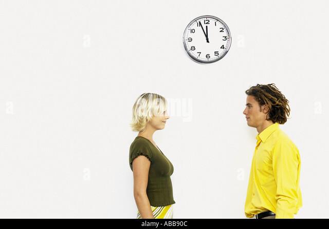 Geschäftsmann und Geschäftsfrau unter Wanduhr Stockbild