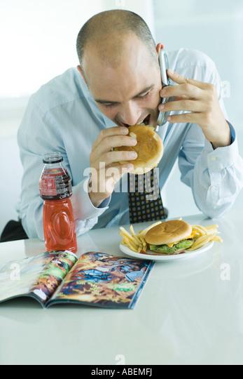 Mann, Hamburger essen, Zelle Telefon benutzen und mit Blick auf Comic-Buch Stockbild