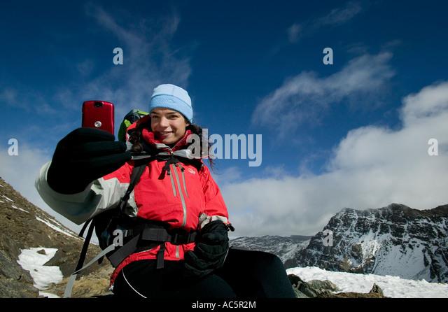 Frau, die ein Bild auf einem red-Kamera-Handy in den Bergen Stockbild