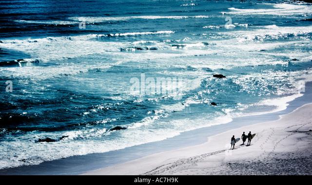 Drei Surfer zu Fuß entlang der Strandpromenade Stockbild