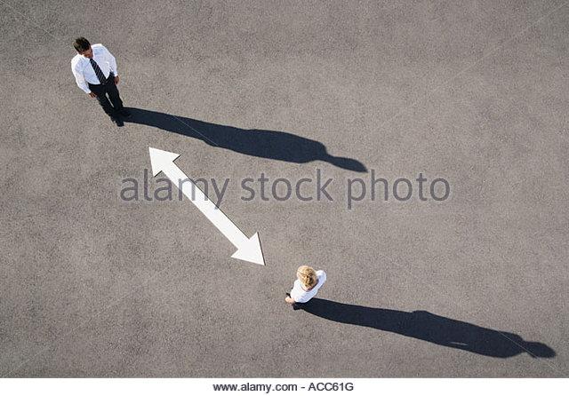 Luftaufnahme von Mann und Frau mit Pfeil auf Bürgersteig Stockbild