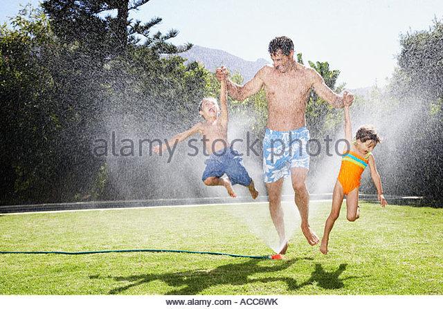 ein Vater mit seinen Kindern in eine Sprinkleranlage zu spielen Stockbild