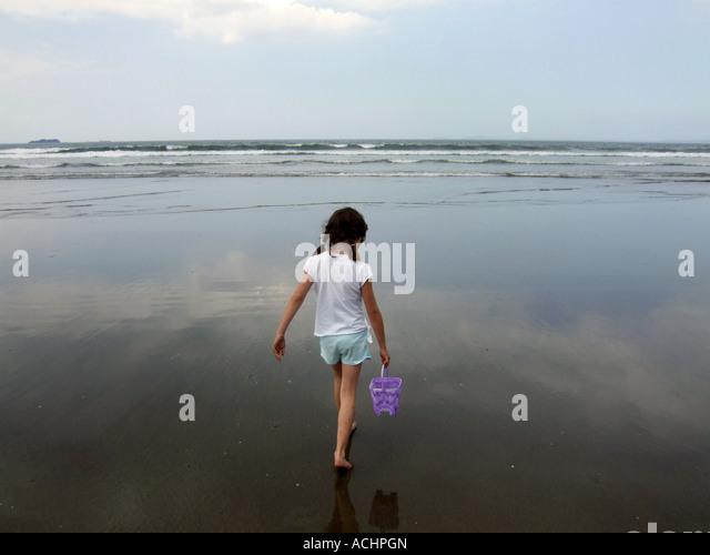 Mädchen, die zu Fuß aus dem Meer mit einem Eimer, UK Stockbild