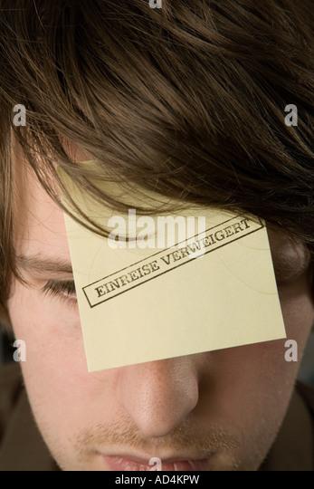 """Ein Mann mit einem Klebstoff Hinweis auf seiner Stirn gestempelt """"Eintrag verweigert"""" Stockbild"""