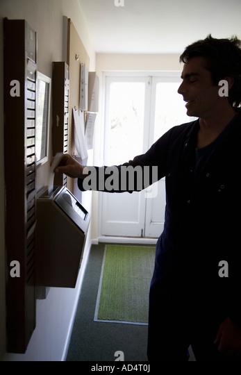 Ein Mann eine Schaltuhr eine Stempelkarte einfügen Stockbild
