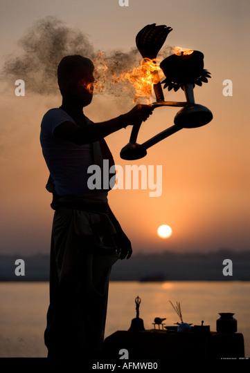 Hinduistischen heiligen Mann Durchführung einer religiösen Zeremonie Puja zum Sonnenaufgang am Ufer des Stockbild