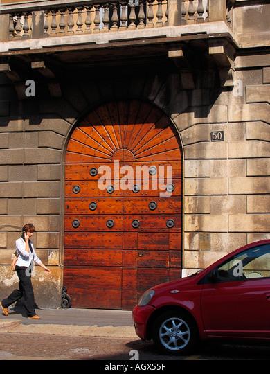 Frau am Handy vorbeigehen Holztür Mailand Italien Stockbild