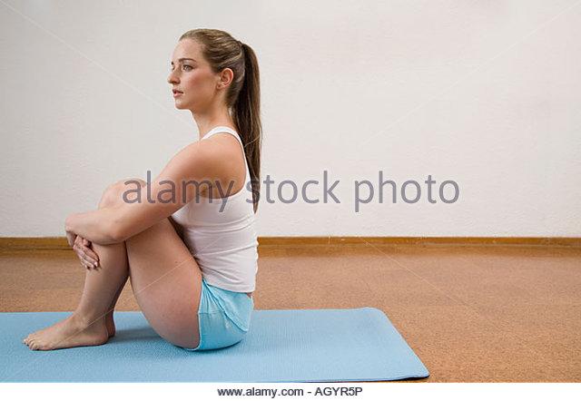 Frau sitzt auf Yoga-Matte Stockbild