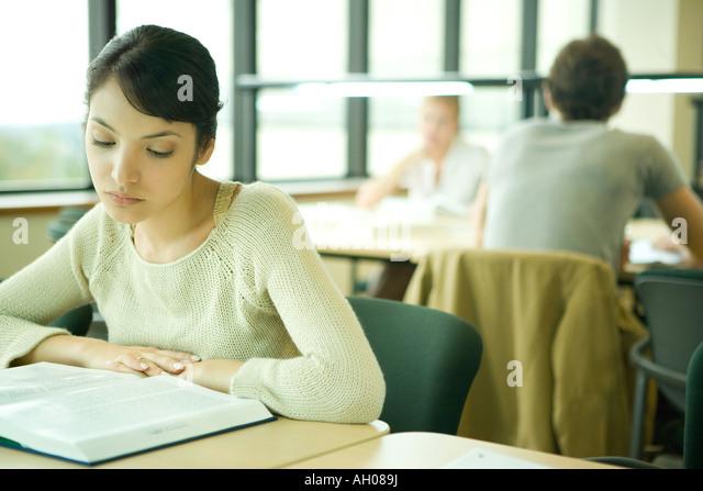 Junge Frau, die in der Universitätsbibliothek zu studieren Stockbild