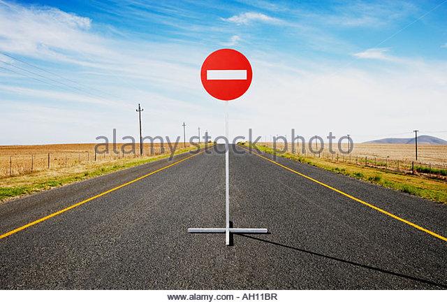 Ein einzelnes Straßenschild auf einer verlassenen Straße Stockbild