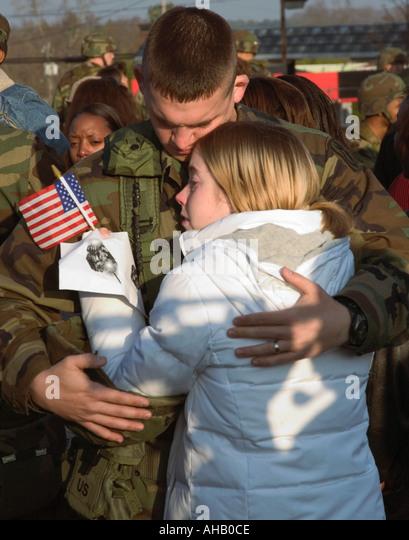 Soldat, 20 bis 24 verlassen für Einsatz in den Irak Hiis Frau umarmt hält uns USA Flagge Stockbild