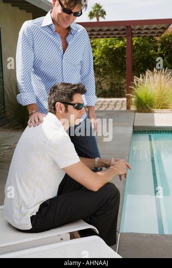 Gay paar sitzt am Swimmingpool Stockbild