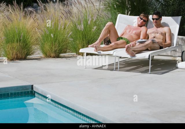 Gay paar entspannende Swimmingpool Stockbild