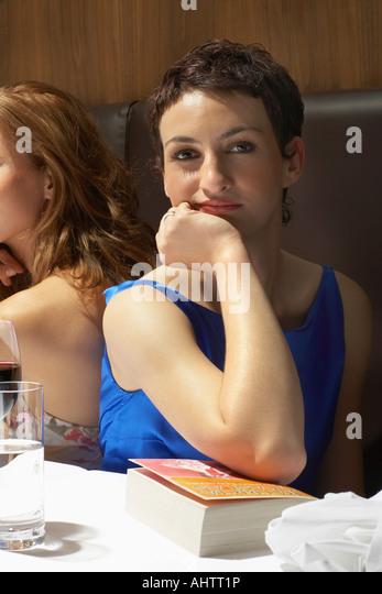 Zwei Frauen in einem Restaurant mit einem Buch Stockbild