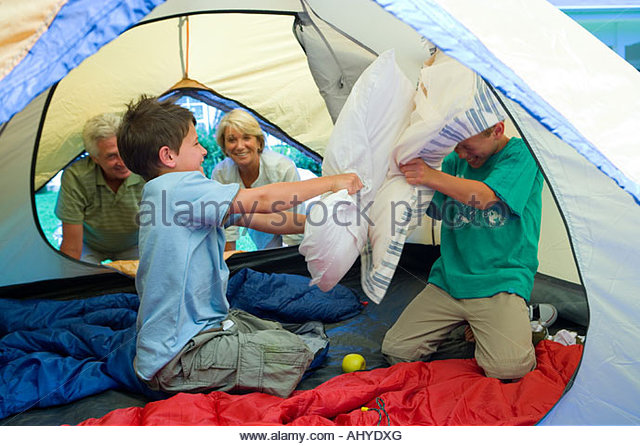 Zwei jungen 8-10, die Kissen zu kämpfen, im Zelt auf der Wiese im Garten Großeltern kniend im Eingang Stockbild