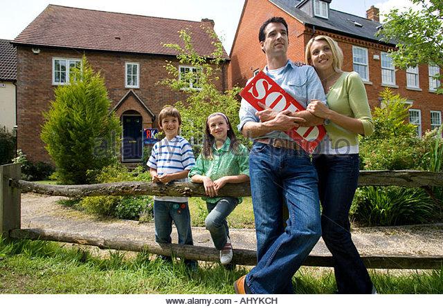 30er Jahre Familie mit verkauften Zeichen und Haus im Hintergrund, Stockbild
