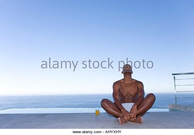 Junger Mann sitzt im Schneidersitz am Boden im Freien auf dem Seeweg, nachschlagen Stockbild
