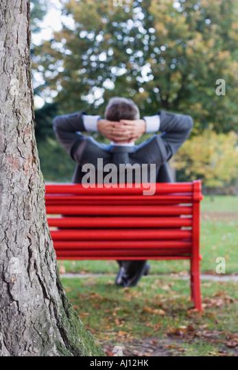 Entspannen Sie sich auf einer roten Parkbank Fokus auf dem Baum im Vordergrund Geschäftsmann Stockbild