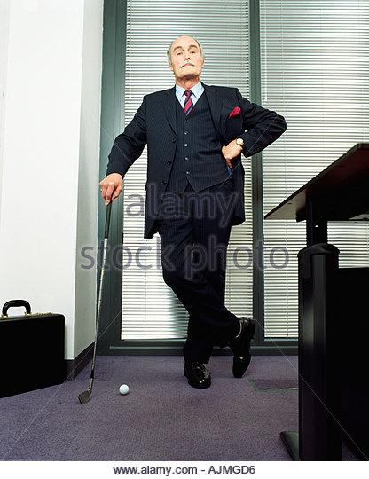 Geschäftsmann, stützte sich auf Golf club Stockbild