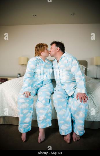 Paar in passenden Pyjamas küssen Stockbild