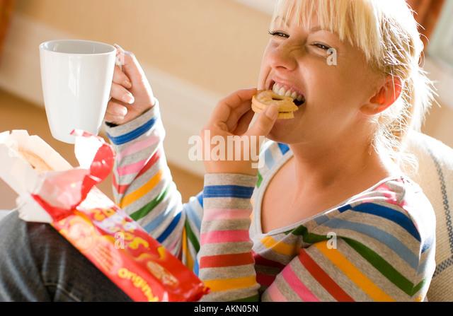 Frau essen Kekse mit Getränk Stockbild