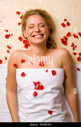 Deutschland, junge Frau liegend auf Massagetisch, Blütenblätter auf Brust Stockbild