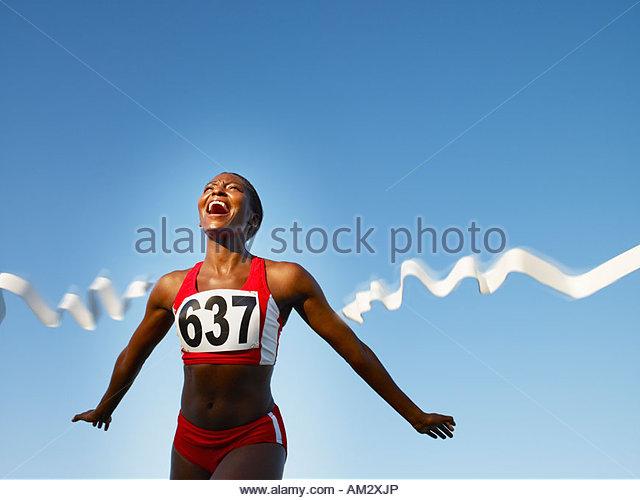 Racer, die Überquerung der Ziellinie lächelnd Stockbild