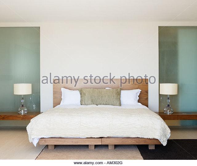Modernes Doppelbett mit Nachttischen Stockbild