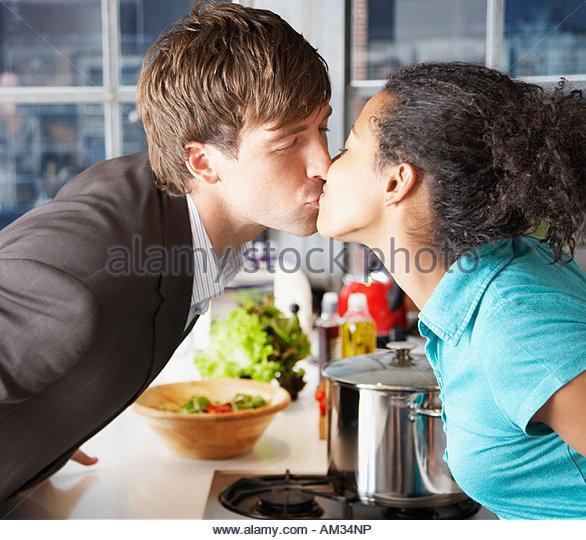 Paar küssen in Küche über Zähler - Stock-Bilder