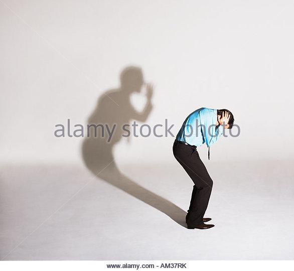 Mann wird von seinem Schatten Schalt Stockbild