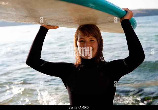 Frau stehend mit einem Surfbrett über ihrem Kopf lächelnd. Stockbild