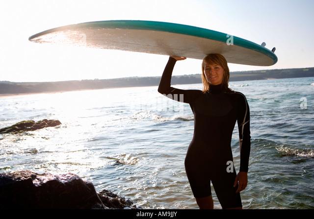 Frau mit einem Surfbrett über den Kopf. Stockbild