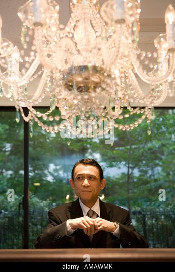 Ein Geschäftsmann stand unter einem Kronleuchter Stockbild