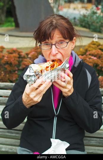 Frau Essen ungesunde Fertigkost Stockbild