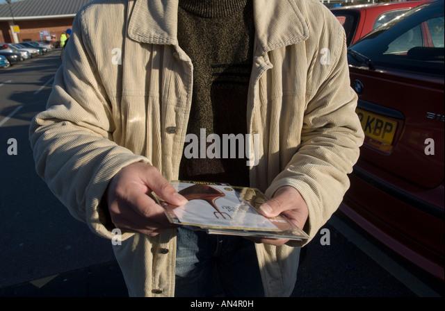 Ein Mann bietet illegale Pirate dvds von Hollywood Filmen in einem Supermarkt in London Stockbild