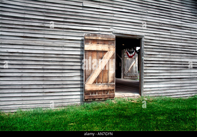 Verwitterte Scheune. Eine Tür ist offen, so dass des Betrachters zu sehen, die roten, weißen & blauen Stockbild