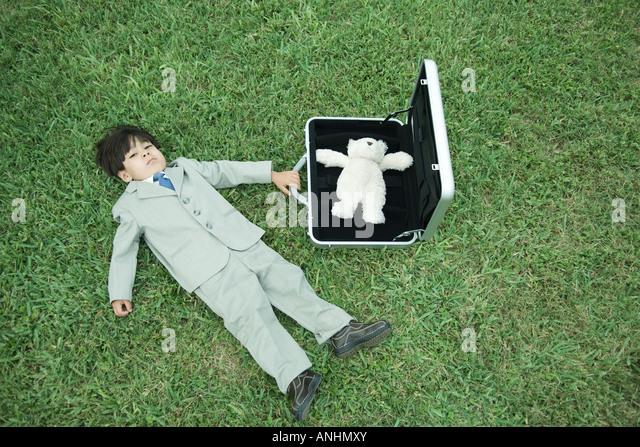Kleiner Junge in voller Farbe, liegend auf dem Rasen neben offenen Aktentasche mit Teddybär Stockbild