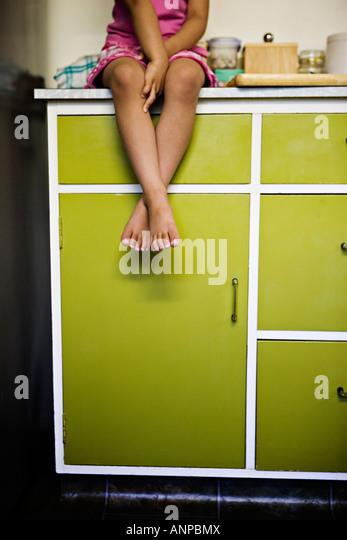 Mädchen sitzt auf der Küchenarbeitsplatte Stockbild