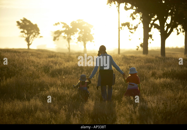 Mother and children wandering through high gras, sunset at the Westcoast, near Haast, South Island, New Zealand Stockbild