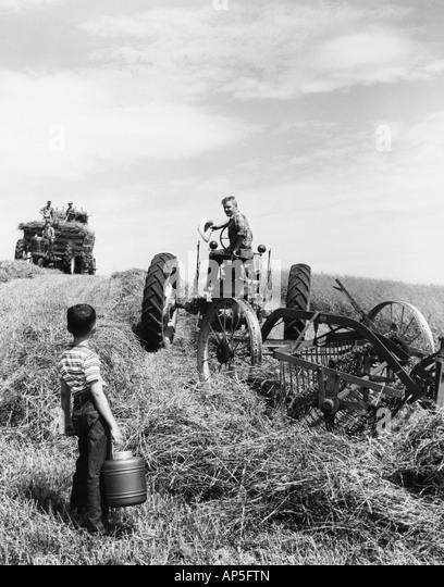 Kleiner Junge bringt Wasser zum Vater, der die Felder auf einem Traktor arbeitet Stockbild