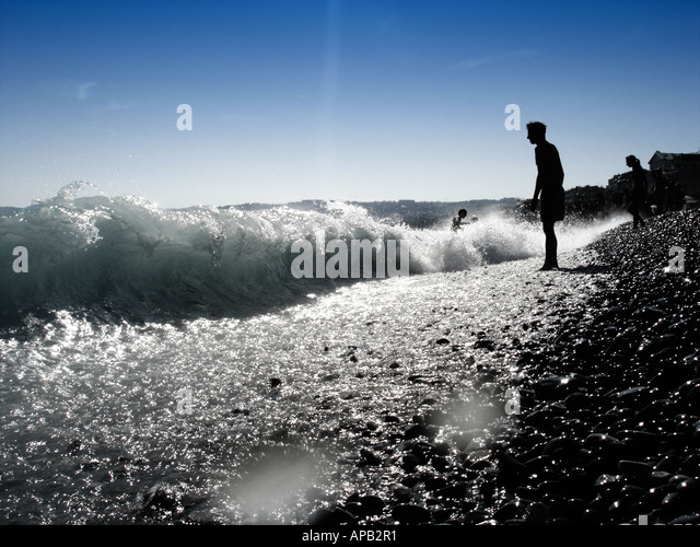 Mann steht am Rande einer Kies direkt am Meer Stockbild
