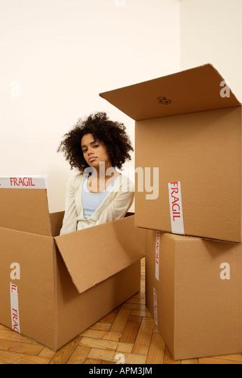 Junge Frau in einem cardbox Stockbild