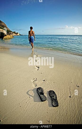 Frau zu Fuß nach unten Strand zum Meer Schuhe und Fußabdrücke Modell veröffentlicht Anse Source Stockbild