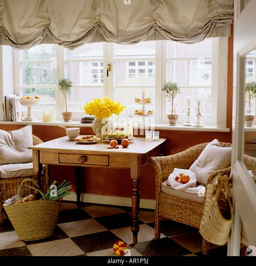 Tisch und Sessel durch ein Fenster mit österreichischen Jalousien Stockbild