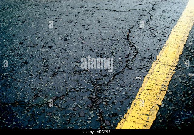 Einzelne gelbe Linie auf rissigen Asphalt Straße. England-UK Stockbild