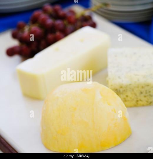 Nahaufnahme der Käsescheiben mit roten Trauben auf ein Schneidebrett Stockbild