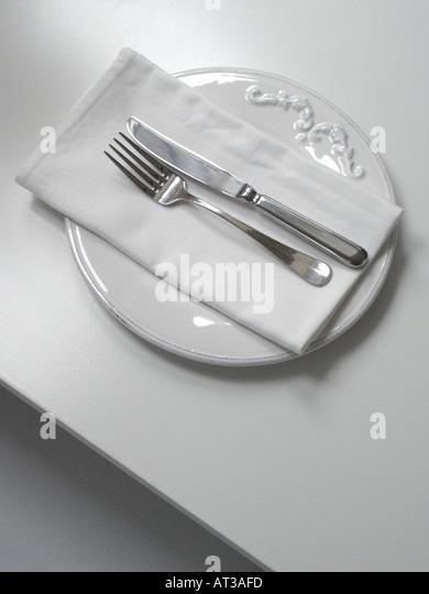 Vertikale Schuss eines weißen dekoriert einfach Platte mit Serviette Silber Messer und Gabel auf einem weißen Stockbild